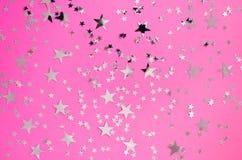 Étoiles argentées de différentes tailles sur un fond rose photographie stock libre de droits