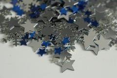 Étoiles argentées et bleues et fond argenté de flocons de neige Photographie stock