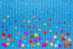 Étoiles colorées de différentes tailles sur un fond bleu de knit Photographie stock libre de droits