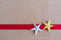 Étoiles d'or et argentées de Noël et ruban rouge sur le panneau de liège Photographie stock libre de droits