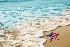 Étoiles de mer avec le drapeau des Etats-Unis sur la plage sablonneuse pour le concept de Fête du travail Photographie stock