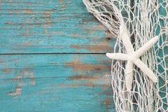 Étoiles de mer en filet de pêche avec un sha en bois de fond de turquoise Photographie stock