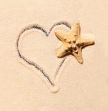 Étoiles de mer et coeur dessinés sur le sable Photo stock