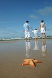 Étoiles de mer et famille tranquille sur la plage Photo libre de droits