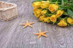 Étoiles de mer et roses oranges sur un fond en bois Images stock
