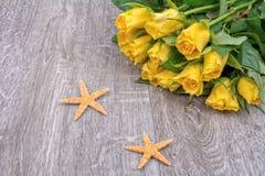 Étoiles de mer et roses oranges sur un fond en bois Photos libres de droits