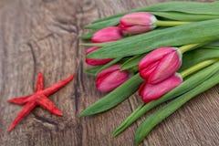Étoiles de mer et tulipes sur un fond en bois Images stock
