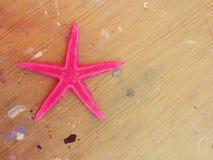 Étoiles de mer roses sur le fond en bois Photo libre de droits