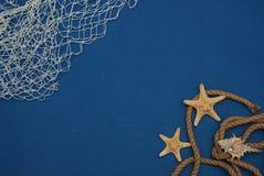 Étoiles de mer, Shell, pierres, corde et filet sur un fond bleu avec l'espace de copie Été Holliday Nautique, concept de Marrine photographie stock libre de droits