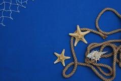 Étoiles de mer, Shell, pierres, corde et filet sur un fond bleu avec l'espace de copie Été Holliday Nautique, concept de Marrine photos libres de droits