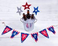 Étoiles et bannière de vacances avec un seau en métal de bière glacée dessus Photo stock