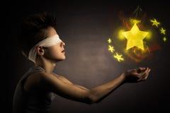 Étoiles rougeoyantes au-dessus des mains ouvertes d'un garçon aveugle Photographie stock libre de droits