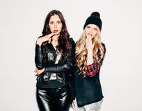 Étonné deux jeunes amies tenant ensemble le nex au mur blanc et ayant l'amusement Représentation des signes avec des mains regard Photos stock