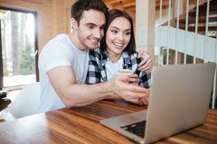 Étreignant les couples s'approchent de l'ordinateur portable Images stock