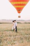 Étreignant les nouveaux mariés heureux tête à tête habillés dans le style de vintage se tiennent dans l'avant de l'airballoon de  Photo libre de droits