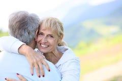 Étreindre aîné de sourire de couples Photo stock