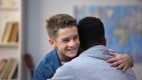Étreindre afro-américain et européen d'adolescents, heureux de se voir clips vidéos
