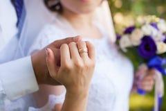 Étreindre d'homme et de femme, tenant des mains avec l'anneau Photo stock