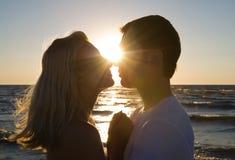 Étreindre de couples, appréciant le coucher du soleil d'été. Photographie stock