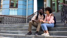 Étreindre de couples d'étudiants, se reposant sur des escaliers de bâtiment d'université, amour de la jeunesse images stock