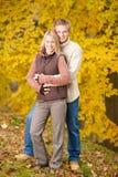 Étreindre de couples d'amour d'automne heureux en stationnement Photographie stock