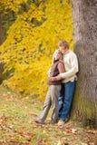 Étreindre de couples d'amour d'automne heureux en stationnement Photographie stock libre de droits