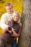 Étreindre de couples d'amour d'automne heureux en stationnement Photos libres de droits