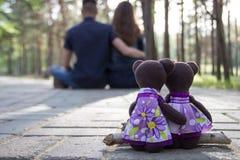 Étreindre de garçon et de fille d'ours de nounours et étreinte se reposante d'homme et de femme dedans Images libres de droits