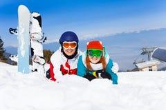 Étreindre des couples dans des masques de ski se trouvant sur la neige Images libres de droits