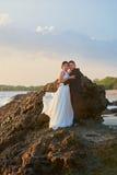 Étreindre des jeunes mariés se tenant sur la roche Photo stock