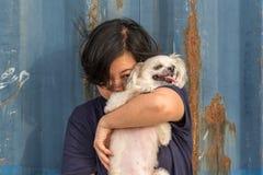 Étreindre heureux asiatique de femme et de chien avec le récipient Photo stock