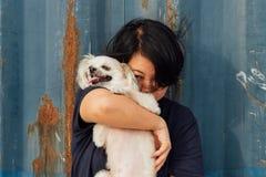 Étreindre heureux asiatique de femme et de chien avec le récipient Photographie stock