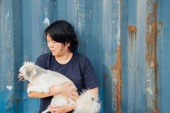 Étreindre heureux asiatique de femme et de chien avec le récipient Images stock