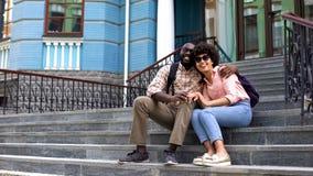 Étreindre heureux de couples d'étudiant, se reposant sur des escaliers de bâtiment d'université, amour de la jeunesse images stock