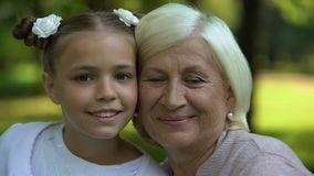 Étreindre heureux de grand-mère et de petite-fille, posant pour la caméra, valeurs familiales clips vidéos