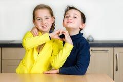 Étreinte d'enfants de mêmes parents formant un coeur avec des mains Images stock