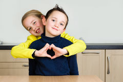 Étreinte d'enfants de mêmes parents formant un coeur avec la main Photo stock