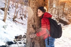 Étreinte de jeune fille un tronc d'arbre en parc d'hiver images libres de droits