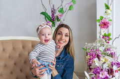 Étreinte de mère et de fille La belle mère avec la fille d'enfant s'asseyent sur un sofa Portrait de studio avec des fleurs Modèl Photographie stock libre de droits