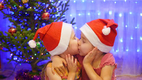 Étreinte et baiser de deux soeurs à la fête de Noël À l'arrière-plan, guirlandes de lumières de sapin Photo stock