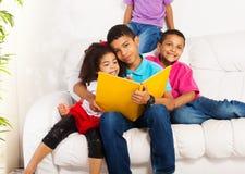 Étreinte et lu à de petits enfants de mêmes parents Images stock