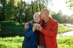 Étreinte et sourire heureux de couples d'aînés ; Photos stock