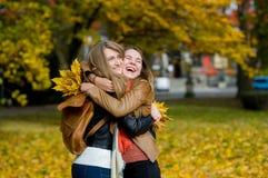 Étreinte gentille de deux filles joyeux en parc d'automne Image stock
