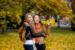 Étreinte gentille de deux filles joyeux en parc d'automne Photographie stock