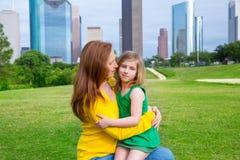 Étreinte heureuse de mère et de fille en parc à l'horizon de ville Photo libre de droits