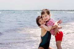 Étreinte supérieure de soeur et de jeune frère sur le bord de la mer Image libre de droits