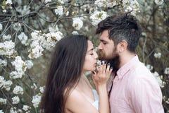 Étreintes d'homme et de femme de concept de date de ressort dans le jardin de floraison la journée de printemps Les couples dans  Images libres de droits