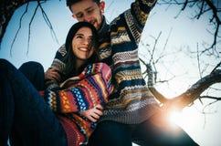 Étreintes de couples de bonheur Le jeune homme étreint la fille sur la branche d'arbre images libres de droits