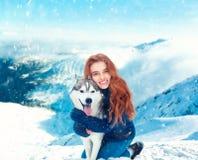 Étreintes de sourire de jeune femme avec le chien de traîneau image libre de droits