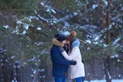 Étreintes heureuses de jeune homme et de femme dans la forêt d'hiver Photographie stock libre de droits